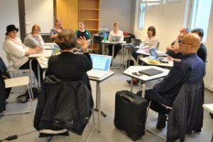 Staff members sit at individual desks in a circle