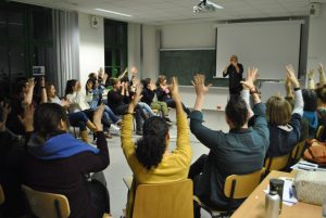 students sitting in a circle applauding in sign language with hands in the air